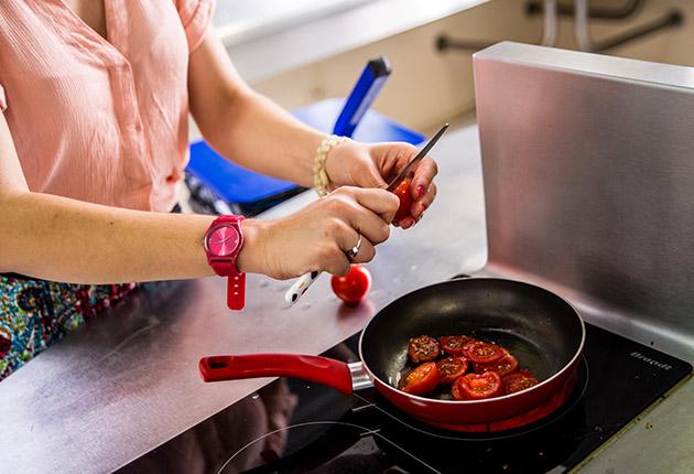 Etudiante cuisinant dans la cuisine commune de la Résidence J. Lejeune, Paris (75015)